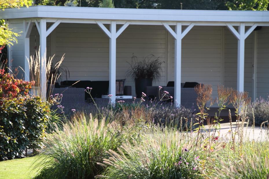 Tuin met overkapping: De witgeschilderde veranda biedt plaats aan een loungeset.